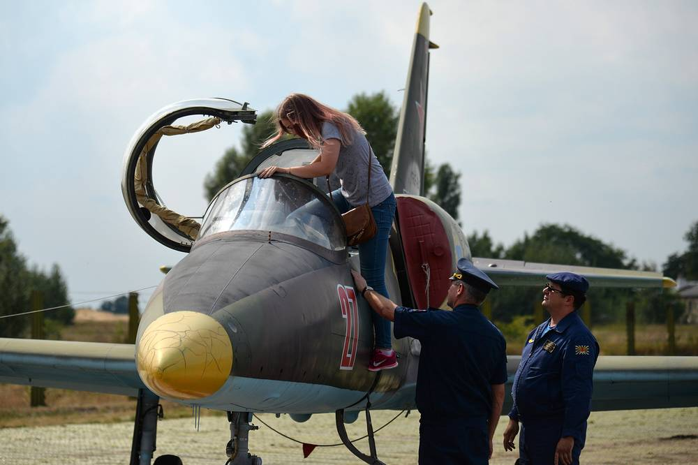 A girl climbs into the cockpit of an aircraft during a tour of Air Force Academy named after Nikolai Zhukovsky and Yuri Gagarin in Voronezh