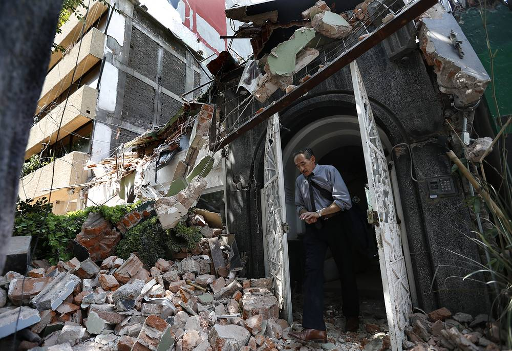 A man walks out of the door frame of a building that collapsed after an earthquake, in the Condesa neighborhood of Mexico City