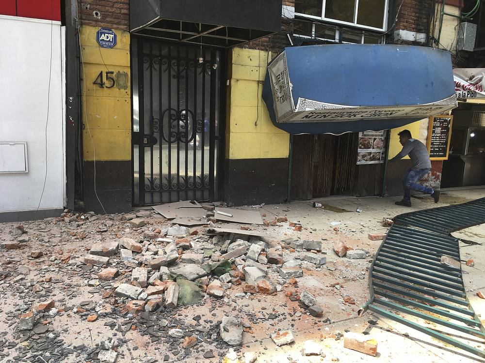 A man enters a damaged building in Mexico City