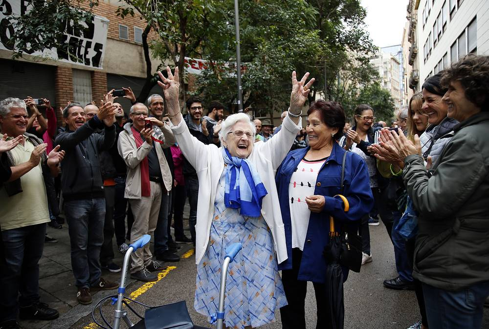An elderly lady is applauded as she celebrates after voting at the Gracia neighborhood in Barcelona