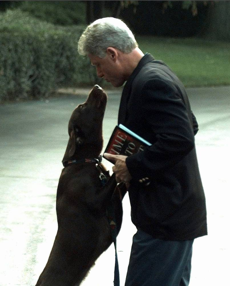 US President Bill Clinton is greeted by his dog Buddy as he returns to the White House, 1998