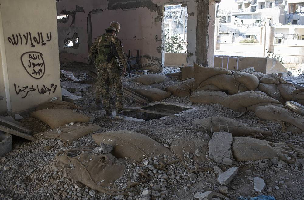 Members of the Syrian Democratic Forces check for bombs at the stadium in Raqqa