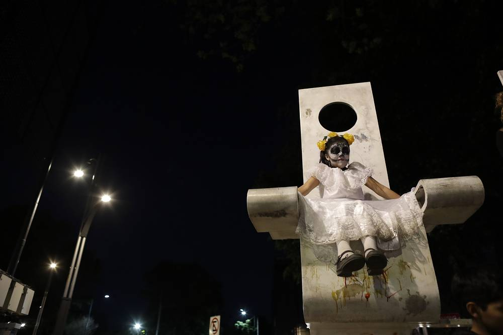 """A girl dressed as Mexico's iconic """"Catrina"""" sits on a piece of public art during a march in the Grand Procession of the Catrinas in Mexico City"""