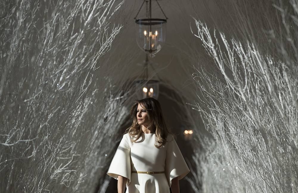 """US First lady Melania Trump walks along the East Colonnade decorated in white branches that are part of 2017 holiday decorations with the theme """"Time-Honored Traditions"""" at the White House in Washington, USA, November 27"""