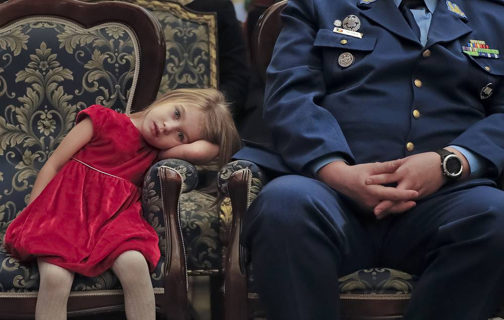 A girl pauses during a Christmas show for children of Romanian military families, in Bucharest, Romania, December 21