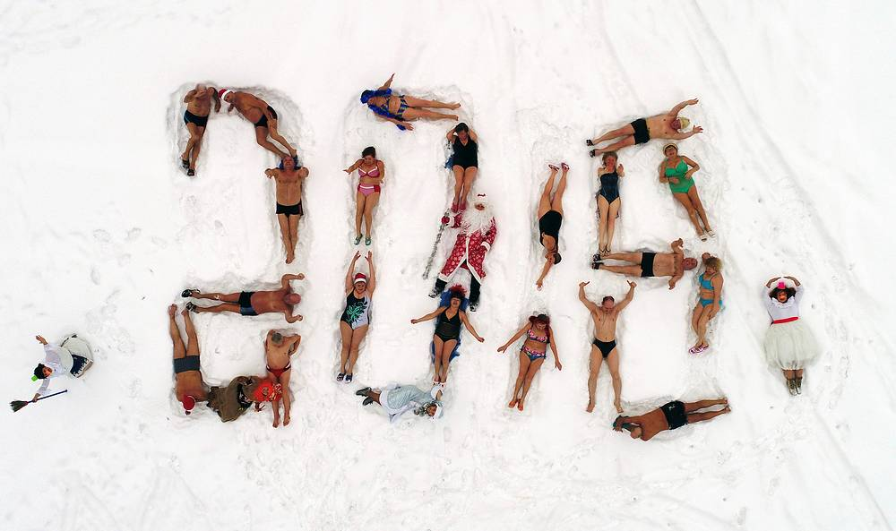 An aerial view shows people dressed as Father Frost, the Russian equivalent of Santa Claus, and Snow Maiden with members of the Cryophile winter swimming club forming with their bodies a 2018 sign on the bank of the Yenisei River to mark the upcoming New Year and Christmas season in the Siberian city of Krasnoyarsk, Russia, December 24