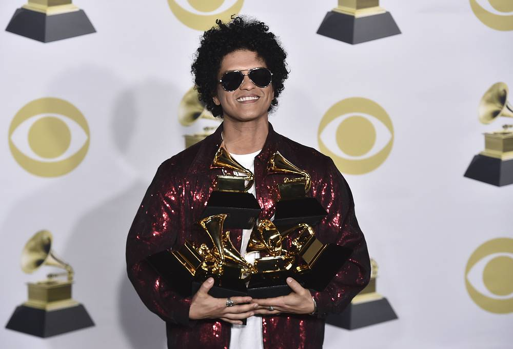 """Bruno Mars poses with his awards for best R&B album, record of the year, album of the year, best engineered album, non-classical, for """"24K Magic,"""" and song of the year, best R&B performance and best R&B song, for """"That's What I Like"""""""