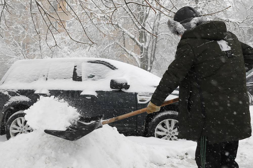 A man digs his car out of the snow in Moscow