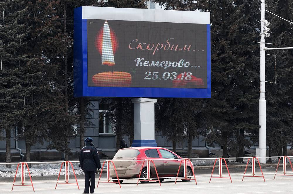 A screen featuring a candle seen by the Kemerovo region administration building on the day of mourning