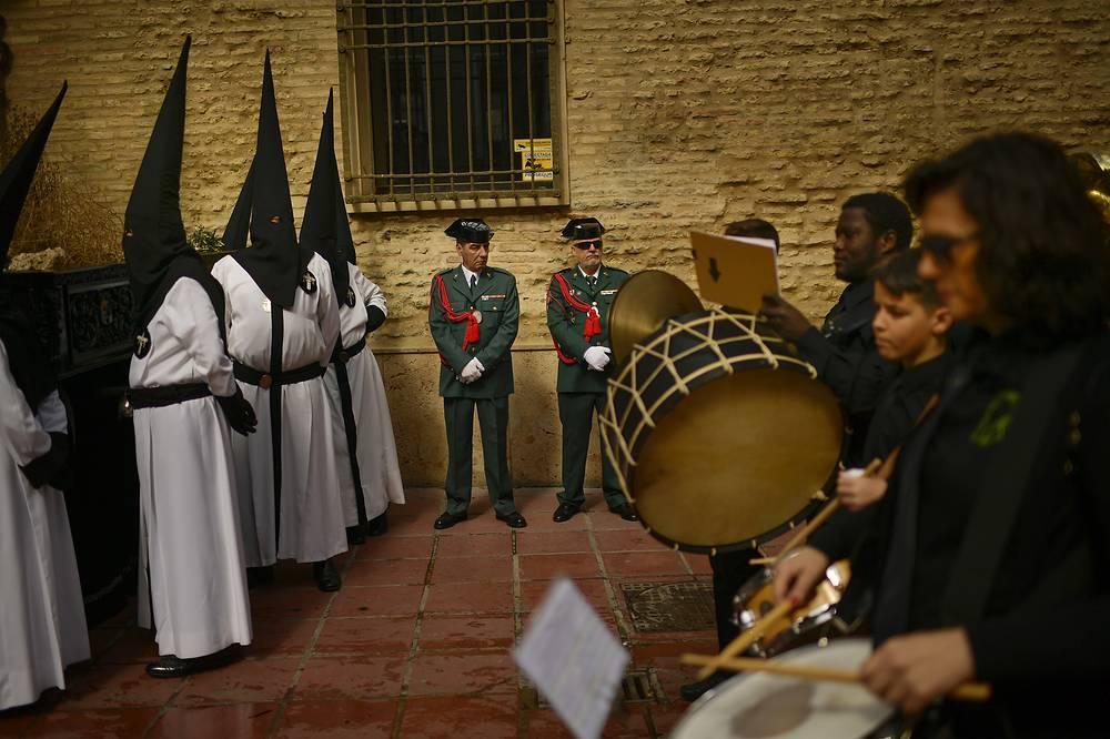 "Spanish Civil Guards, penitents and musicians take part in the procession of the ""Exaltacion de La Santa Cruz"" brotherhood, during Holy Week in Zaragoza, Spain"
