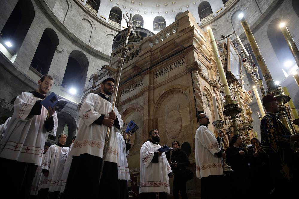 Catholic clergy walk during the Washing of the Feet procession at the Church of the Holy Sepulchre, traditionally believed by many Christians to be the site of the crucifixion and burial of Jesus Christ, in Jerusalem