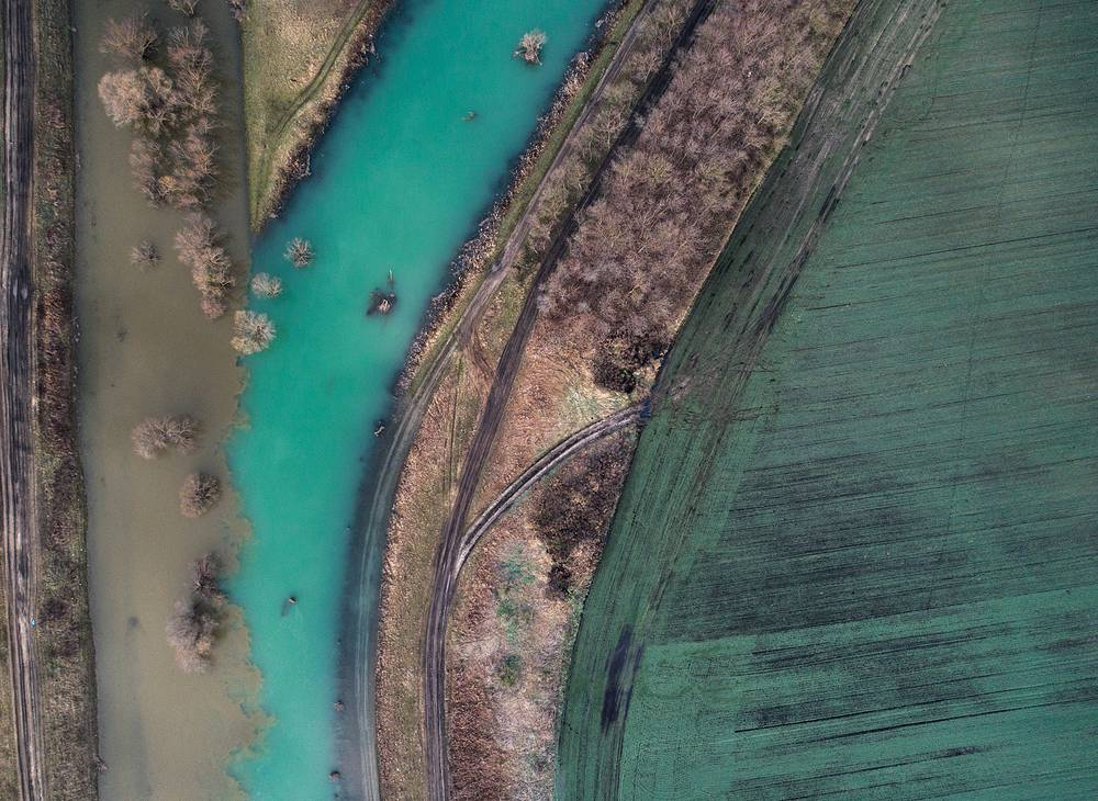 An aerial view shows the mixing of watercourses where the River Kapos enters the Sio canal, the only outflow of Lake Balaton near Tolnanemedi, Hungary, March 26