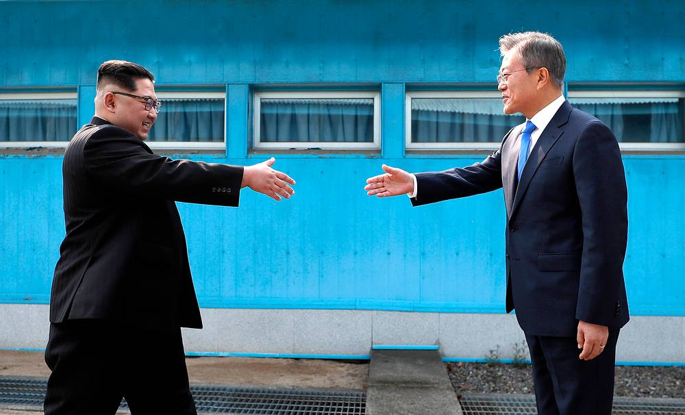 North Korean leader Kim Jong Un prepares to shake hands with South Korean President Moon Jae-in over the military demarcation line at the border village of Panmunjom in Demilitarized Zone, April 27