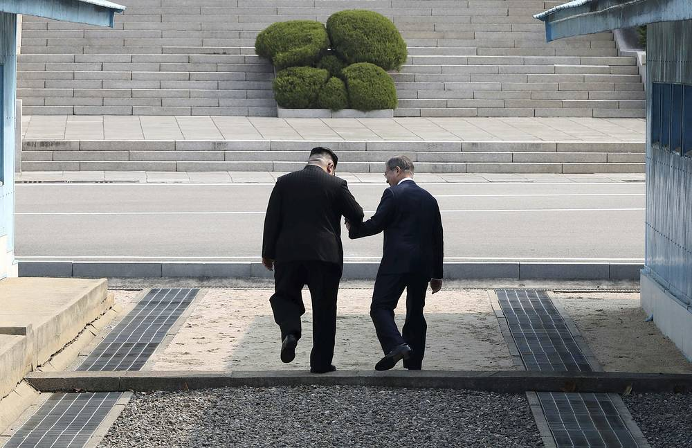 North Korean leader Kim Jong Un and South Korean President Moon Jae-in cross the demarcation line at the border village of Panmunjom in the Demilitarized Zone, April 27