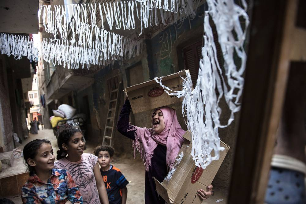 Children helping put up Ramadan ornaments along the streets of Baragel, in the outskirts of Cairo, Egypt, May 12