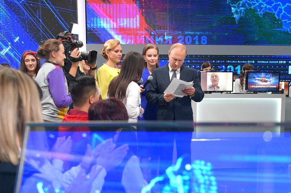 Russia's President Vladimir Putin looks through papers during his annual Q&A session