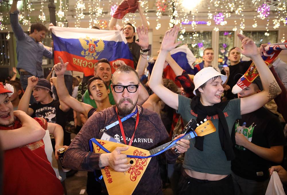 Russian football fans celebrate their team winning a match against Egypt, in Moscow