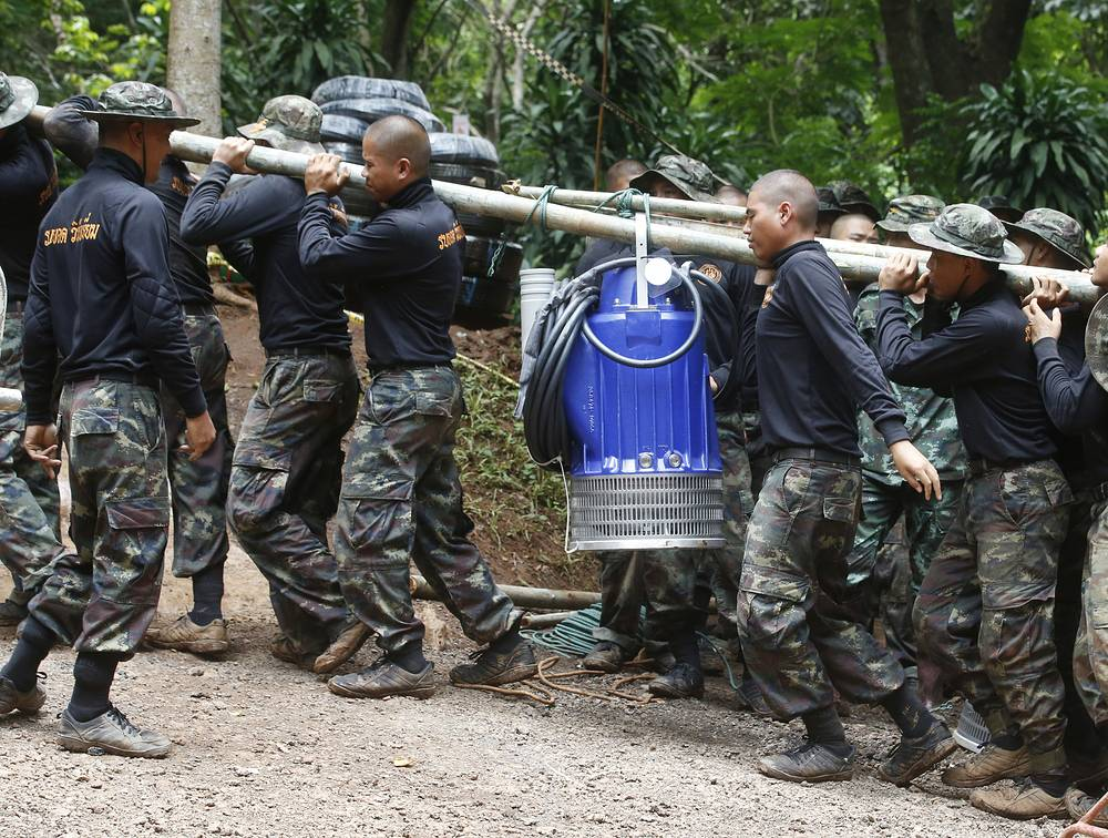 Soldiers carry a pump to help drain the rising flood water in a cave