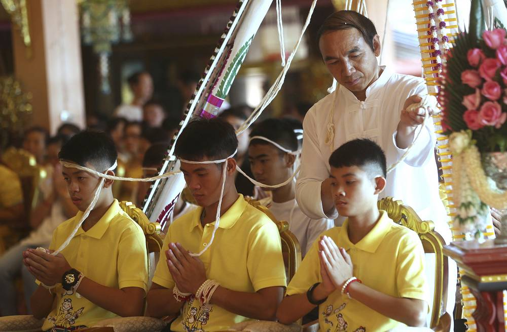 Coach Ekkapol Janthawong and members of the rescued football team attend a Buddhist ceremony that is believed to extend the lives of its attendees as well as ridding them of dangers and misfortunes in Mae Sai district, Chiang Rai province, July 19,. The 12 boys and their coach were rescued from a cave in northern Thailand