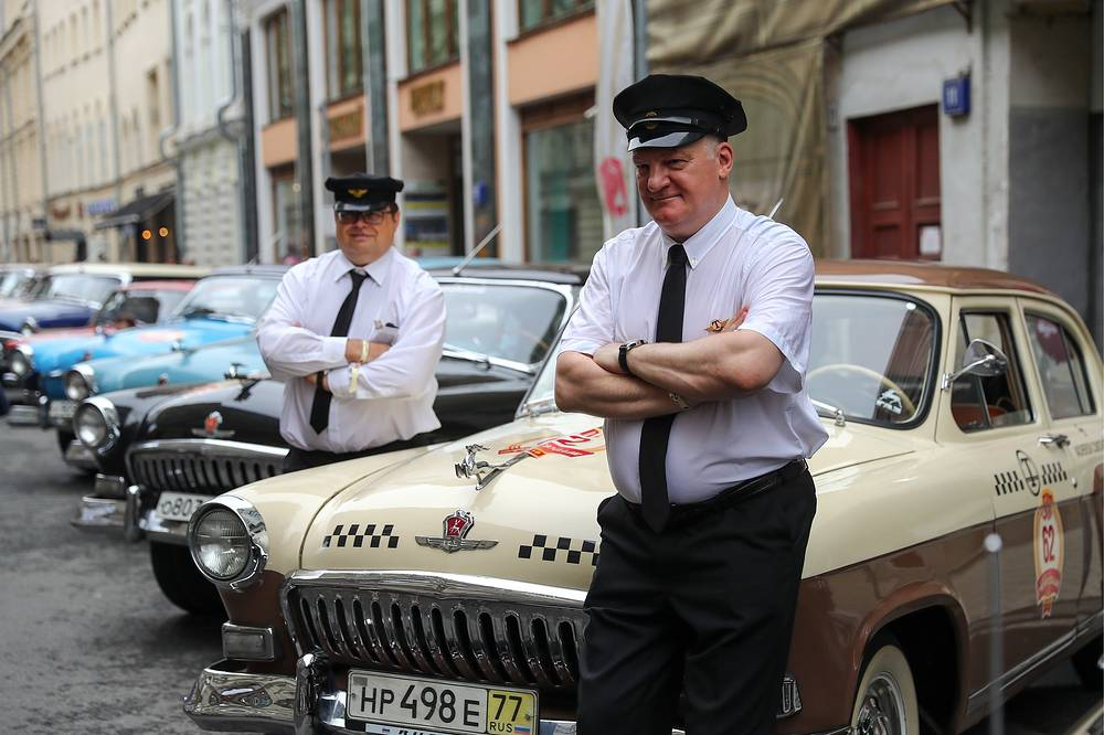 Participants dressed up as Soviet taxi drivers outside a Volga GAZ-21T car in Vetoshny Pereulok Street