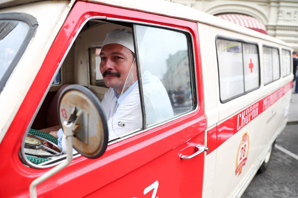 A participant dressed up as a medical worker sits in a classic RAF-977 ambulance car