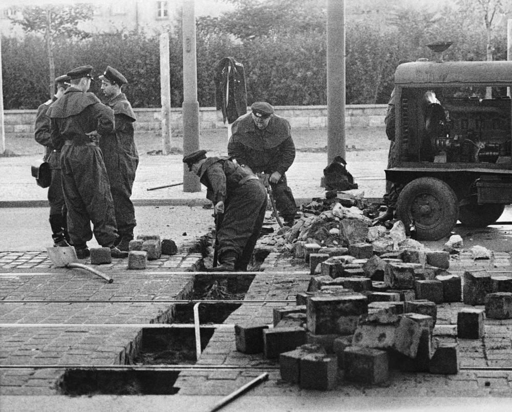 Members of the East German military remove paving blocks on Friedrich Strasse in East Berlin as East Germany tightened the border crossing, 1961