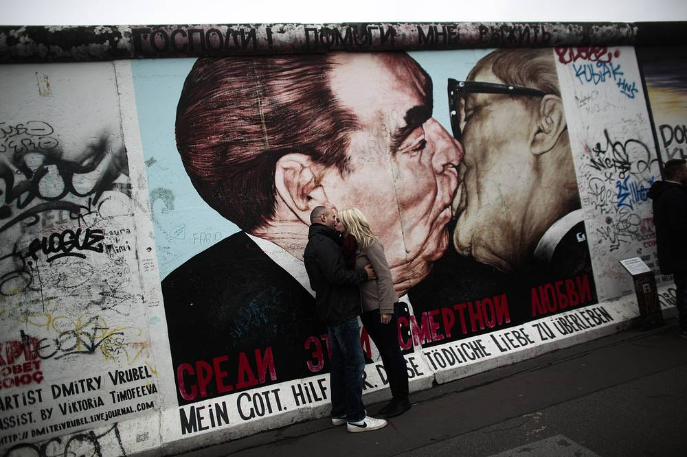 A couple kiss in front of a painting of former Soviet leader Leonid Brezhnev, and long time East German communistic leader Erich Honecker at the East Side Gallery, the largest part of original remains of the Berlin Wall, 2014