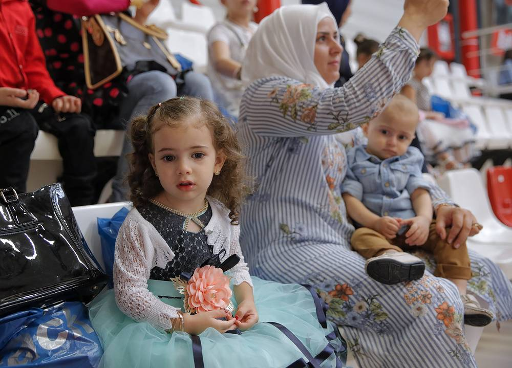 A girl sits in the women's section during Eid al-Adha prayers, held in a sports hall in Bucharest, Romania