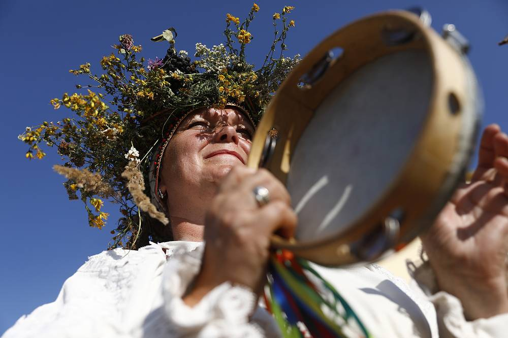 A woman wearing a flower crown plays tambourine