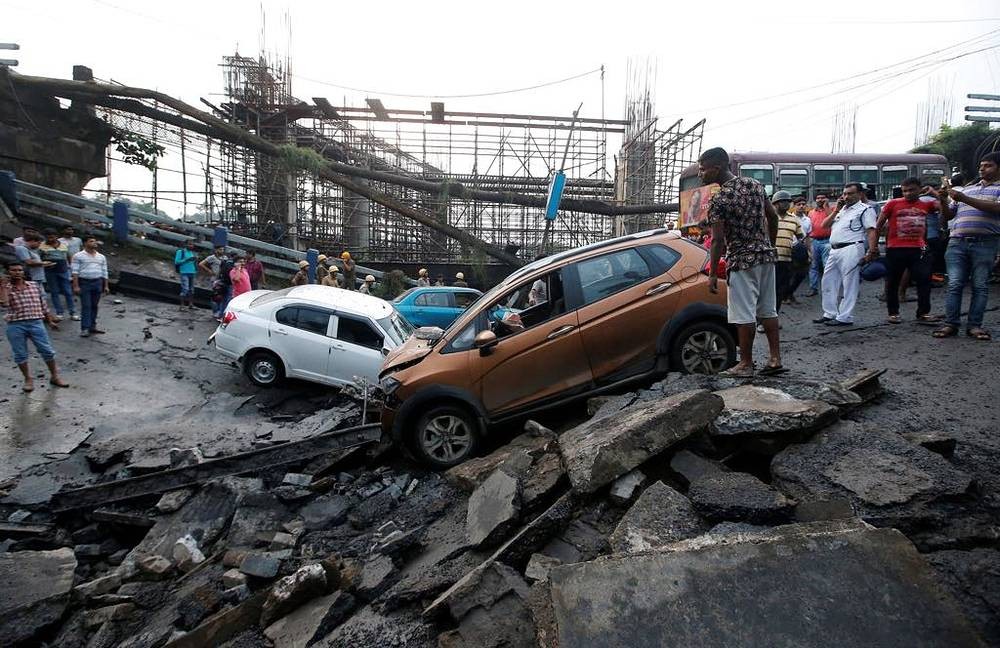 People stand next to the wreckage of vehicles at the site of a bridge that collapsed in Kolkata, September 4