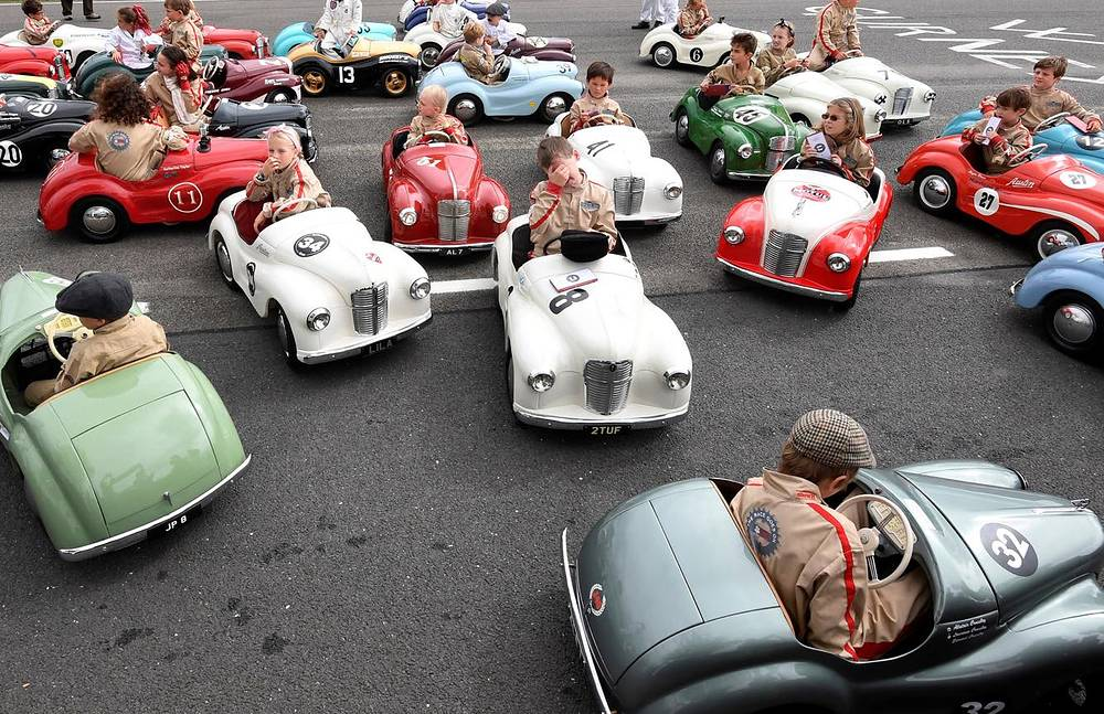 Children react after competing in a pedal car race as motoring enthusiasts attend the Goodwood Revival, a three day classic car racing festival celebrating the mid-twentieth century heyday of the sport, at Goodwood in southern Britain, September 9