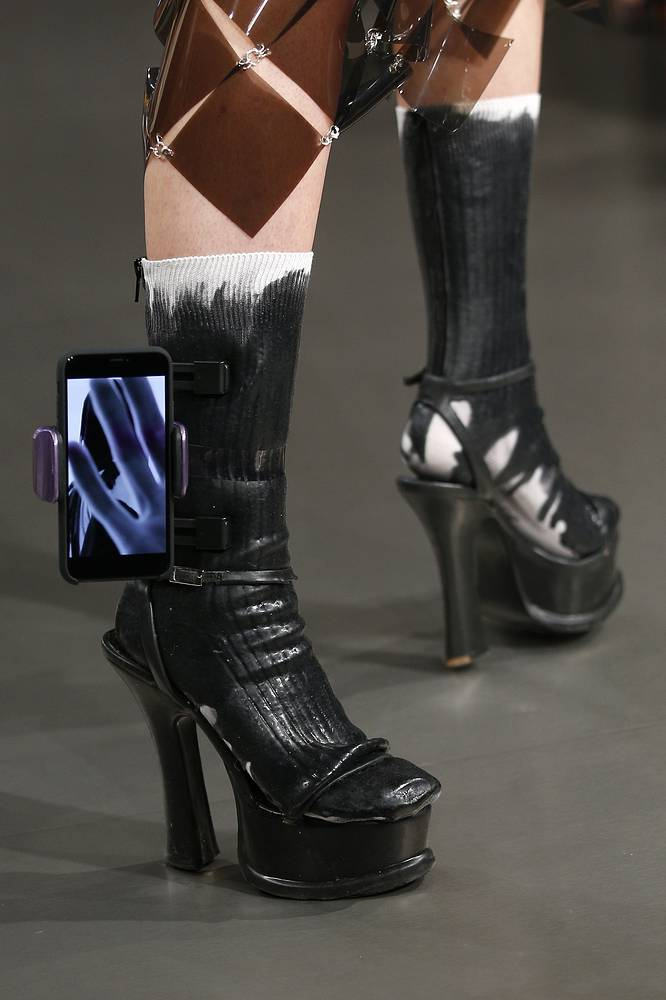 A model has a smartphone attached to her shoe as part of Maison Margiela Spring/Summer 2019 ready-to-wear fashion collection