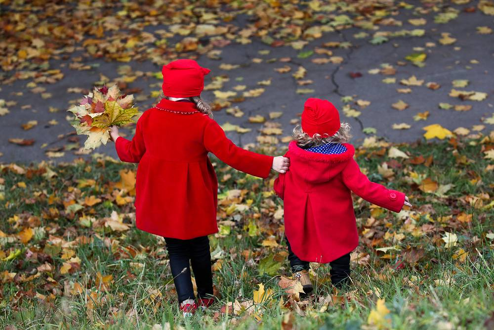 Children collecting fallen maple leaves in Moscow