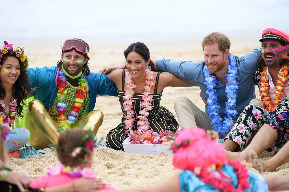 Britain's Prince Harry, the Duke of Sussex and his wife Meghan, the Duchess of Sussex take part in a 'Fluro Friday' session run by OneWave, a local surfing community group raising awareness for mental health and wellbeing, at Bondi Beach in Sydney, October 19