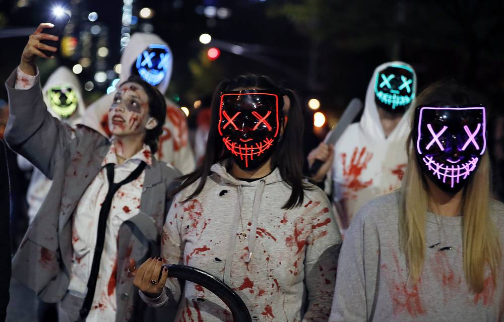 People dressed up in Purge costumes march in New York