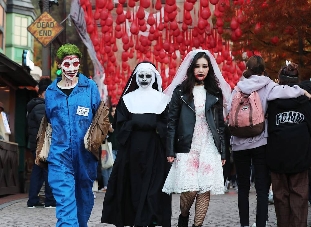 Visitors show off their Halloween costumes in Everland amusement park in Yongin, South Korea