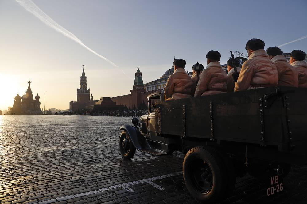 Russian soldiers dressed in historical uniform sit in the back of a GAZ AA during the November 7 parade