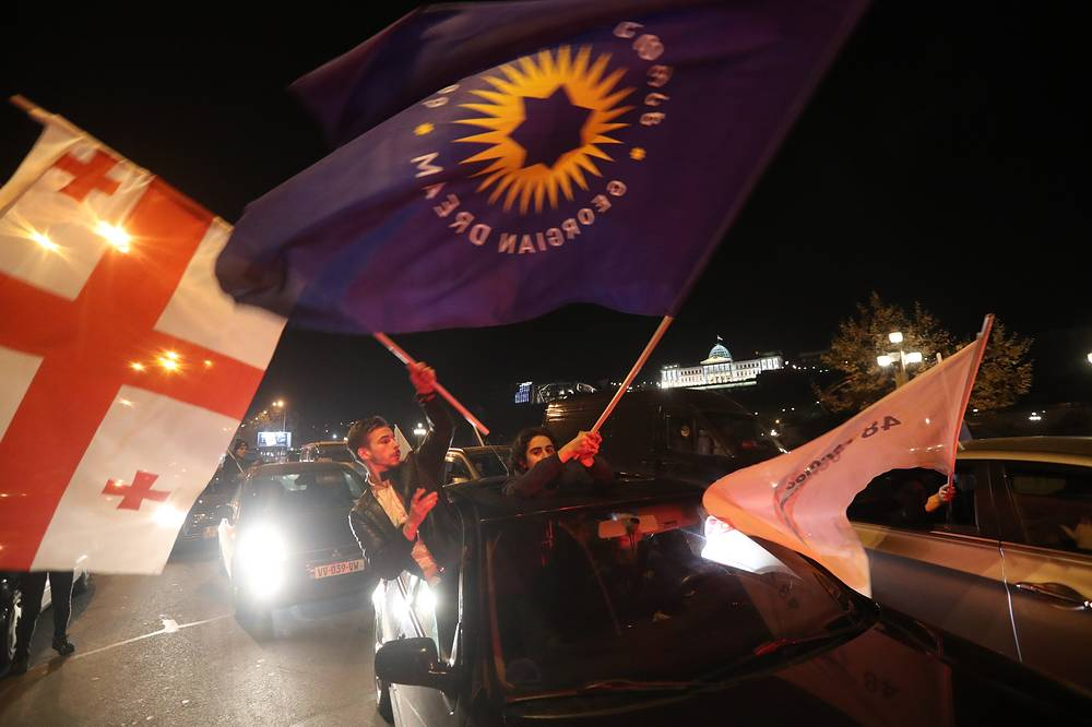 Supporters of independent presidential candidate Salome Zurabishvili, who is backed by the ruling Georgian Dream party, wave the party's flag and Georgian flag while riding a car as they celebrate after announcement of the exit polls following the presidential election in Tbilisi