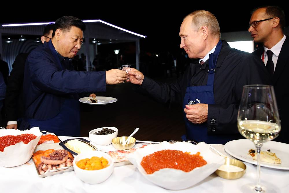 China's President Xi Jinping and Russia's President Vladimir Putin eating Russian pancakes at the Far East Street exhibition on the sidelines of the 2018 Eastern Economic Forum on Russky Island