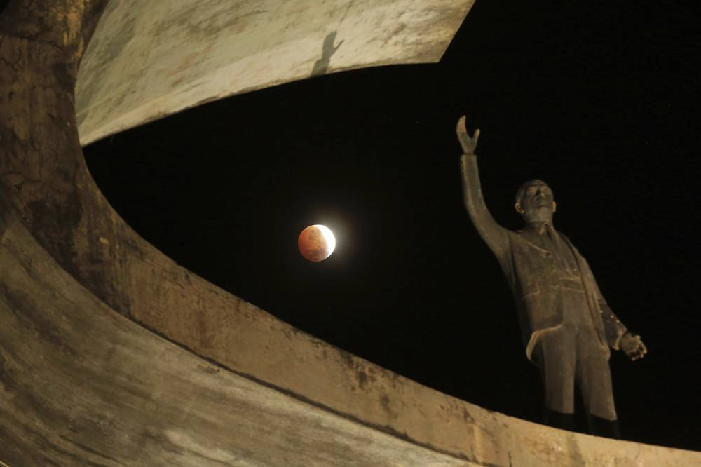 """A lunar eclipse is seen behind the """"Memrial JK,"""" a monument in honor of the founder of Brasilia, Brazil"""