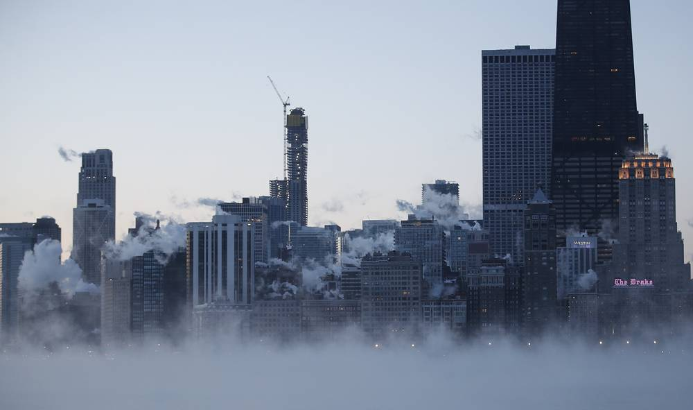 Steam rises from the city as the sun rises in Chicago