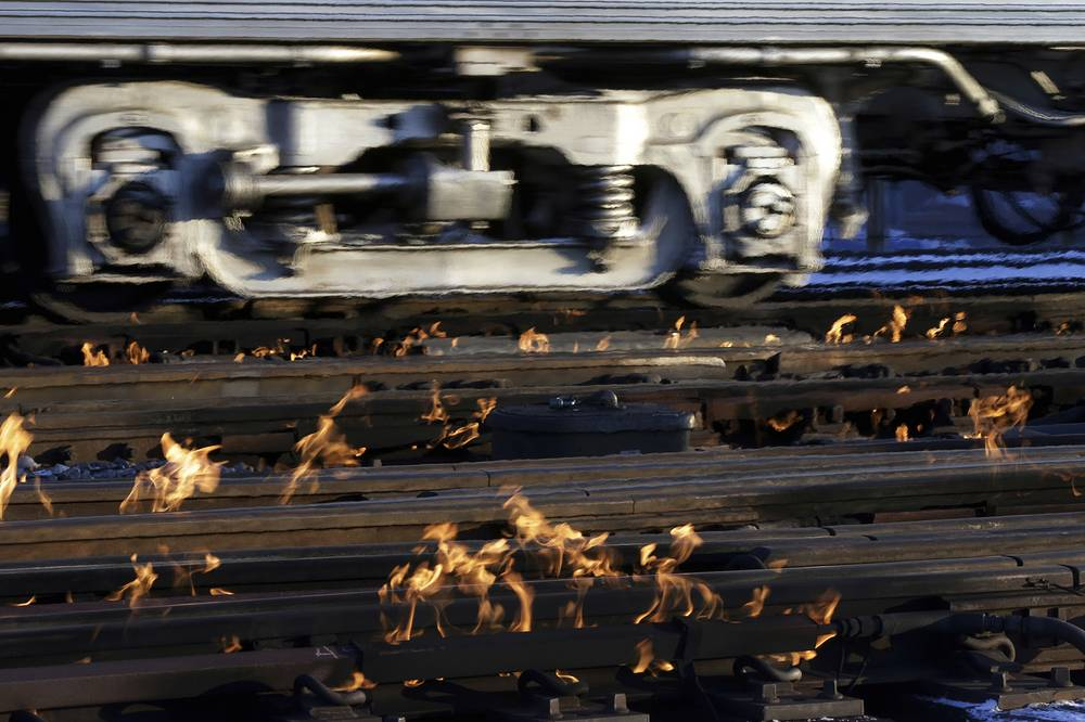 A Metra train moves southbound to downtown Chicago as the gas-fired switch heater on the rails keeps the ice and snow off the switches near Metra Western Avenue station in Chicago