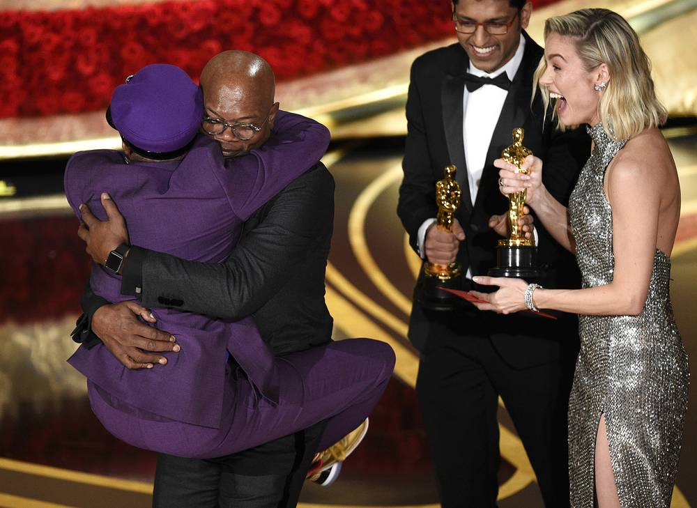 """Samuel L. Jackson embraces Spike Lee, winner of the award for best adapted screenplay for """"BlacKkKlansman"""" as Brie Larson looks on, at the Dolby Theatre in Los Angeles"""