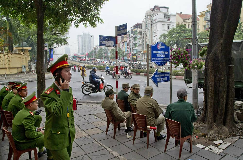 Policemen monitor from a street corner in Hanoi