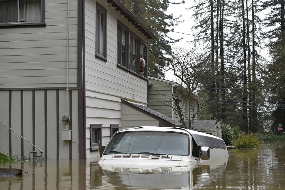 A woman looks out of her window at her van submerged in the flood waters of the Russian River in Forestville