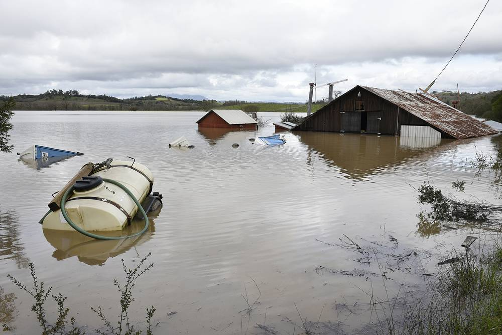 A barn and farm equipment are seen submerged in flood waters from the Russian River in Forestville
