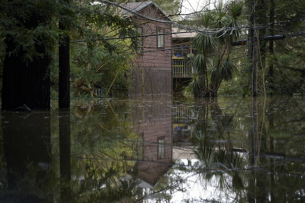 A home is seen reflected in the flood waters of the Russian River in Forestville