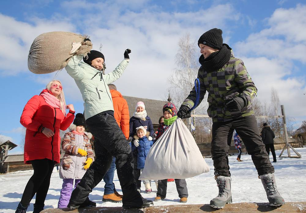 People play sack fighting on a bench during Maslenitsa celebrations in Belarus