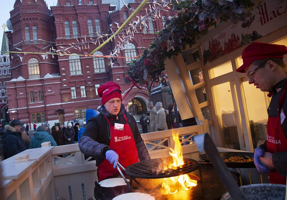 Volunteers cook pancakes during Maslenitsa holiday celebrations near the Kremlin Wall in Moscow