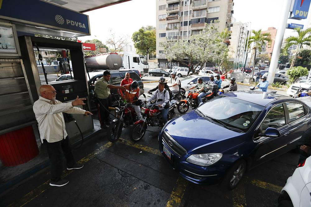 Customers line up at a gas station in Caracas
